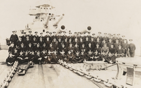 Black and white photograph of the officers and midshipmen of HMS Lion including Prince Louis Francis of Battenberg (later Lord Mountbatten), 1916 [MB2/A12/65]. He can be seen in the uniform of a midshipman, seated cross-legged in the middle of the front row, tenth from the left. He is holding a small dog, probably the ship's mascot.